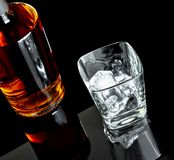 Top of view of empty whiskey glass with ice near bottle on black background Stock Photo