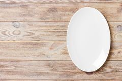 Top view of empty white food plate on a wood background.  Royalty Free Stock Images