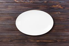 Top view of empty white food plate on a wood background.  Royalty Free Stock Photos