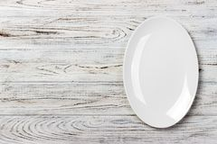 Top view of empty white food plate on a wood background.  Royalty Free Stock Photography