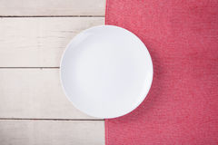 Top view of empty white plate put on red tablecloth and table. Stock Photography