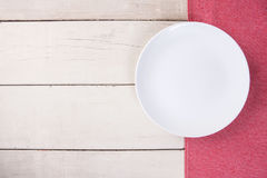 Top view of empty white plate put on red tablecloth and table. Stock Image