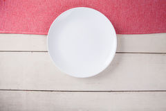 Top view of empty white plate put on red tablecloth and table. Stock Photo