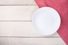 Top view of empty white plate put on red tablecloth. Stock Photos