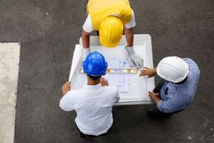Top view of engineering team look plan. Top view of engineering team of site manager, field engineer and foreman looking at  constructed paper blueprint plans at Stock Images