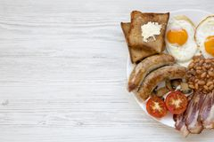 Top view English breakfast with fried eggs, bacon, sausages, beans and toasts. White wooden background. Copy space and text area Royalty Free Stock Photo