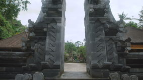 Top view of the entrance to an Asian temple, which is located in a tropical forest with high green palm trees and other. View from the top to down in the stock footage