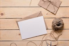 Top view of envelope and blank greeting card. On white wooden background with vintage tone. Twine. Gift wrapping. Send a postcard. Handmade kraft gift cards royalty free stock images