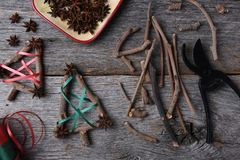 Making Rustic Christmas Decorations. Top view of the equipment and supplies for making rustic Christmas decorations, including twigs, star anise, shears, and Royalty Free Stock Image