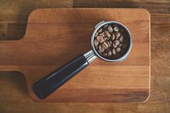 Portafilter with whole specialty coffee beans Royalty Free Stock Photo