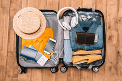 Top view of essentials for tourist with clothes, accessories and gadgets, wallet, passport, smartphone in bag. Ready for travel concept. Top view of essentials royalty free stock photos