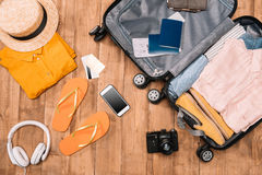 Top view of essentials for tourist with clothes, accessories and gadgets, wallet, passport, smartphone in bag. Stock Photography
