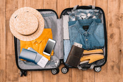 Top view of essentials for tourist with clothes, accessories and gadgets, wallet, passport, smartphone in bag. Stock Photo