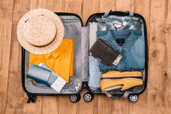 Top view of essentials for tourist with clothes, accessories and gadgets, wallet, passport, smartphone in bag. Royalty Free Stock Images