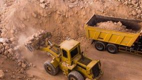 Top view excavator loading crushed rock on dumper truck stock video