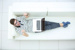 Top view of excited young man using his laptop in bright living. Happy  smiling young man using his laptop Royalty Free Stock Photo