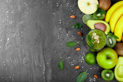 Top view of exotic fruits. Yellow bananas, green kiwis, lime, avocado and cocktail on a spacious background. Copy space. Top view of an assortment of tropical stock photography