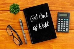 Top view of eyeglasses,calculator,plant,pen and notebook written with Get Out Of Debt on wooden background. Business and finance. stock illustration