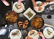 Top view of family eating Spanish Tapas around a white table from high view angle.  Stock Photo