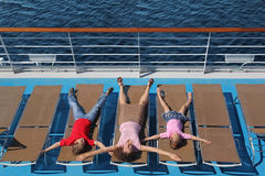 Top view of family lying at deck-chair on ship. Top view of mother, son and little daughter lying at deck-chair on ship and representing starfish Royalty Free Stock Photo