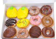 Top view fancy donuts in a box. Top view flat lay of one dozen various plain and fancy donuts in a white box isolated. Are donuts becoming a new fad or the new stock photos