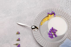 Top view of a fantastic milkshake. A plate with a cool cocktail, flowers and a spoon on a white background. Copy space. Stock Photos