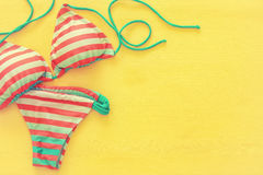Top view of fashion female swimsuit bikini on yellow wooden background Stock Photography
