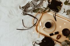 Top view fashion gold and black accessories. Mask, coffee, lipstick and lace lingerie. stock photos