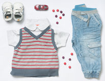 Top view fashion trendy look of baby boy clothes with sweets and. Top view fashion trendy look of baby clothes and toy stuff, baby fashion concept stock photography