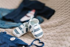 Top view fashion trendy look of baby clothes, fashion concept.  A pair of baby boy shoes. Set of baby clothes and accessories on light background, flat lay stock image