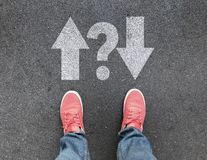 Top view of feet and different direction arrows with question mark on asphalt road stock photos