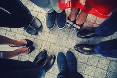 Top view of feet of fashionable, stylish people standing in a circle.  stock photos