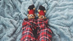 Top of view of feet at home in bed dressed socks with cute teddy bears and in pajamas on a blue blanket. Playing foot at home in bed dressed socks with teddy Royalty Free Stock Images