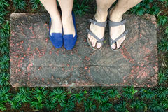 Top view feet of male and female couple lover standing on stone floor among little green grass garden. hipster style.  Royalty Free Stock Photos