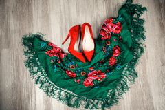 Red and green combination in fashion. Top view female accessories red shoes with high heels and scarf with large flowers Royalty Free Stock Images