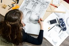 The top view of the female architect designer draws sketches in pencil on white paper. Black and white drawing of an architectural. Top view of the female Royalty Free Stock Images