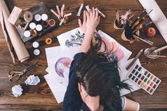 top view of female artist sleeping on sketches and paints royalty free stock photo