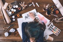 Female artist sleeping on sketches at workplace stock photo