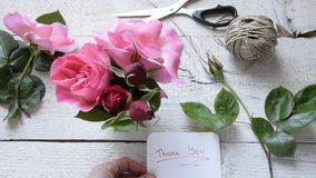 Top view of female decorator holding `Thank you` card, arranging roses on the wooden table. Concepts - fiorist, occupation, hobby, small business stock video footage
