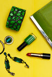 Top view of female fashion accessories . Green handbag with lipstick bracelet earnings necklace Royalty Free Stock Photos