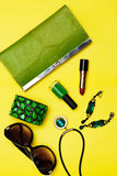 Top view of female fashion accessories . Green handbag with lipstick bracelet earnings necklace Stock Images