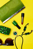 Top view of female fashion accessories . Green handbag with lipstick bracelet earnings necklace Stock Image