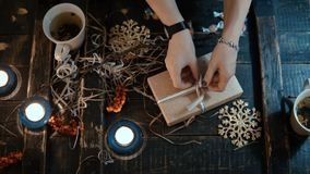 Top view of female hands binds a box with a ribbon, decorating the Christmas present to friend sitting at the table. stock video footage