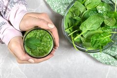 Female holding a glass with a fresh green smoothie stock images