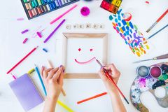 Top view Female Hands drawing smile on canvas with Create word lettering and many colorful paintiing materials on white background. Add colors to your life, be stock image