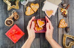 Top view female hands holding box with homemade cookies in form of hearts as gift for a loved one. Wooden table with greeting card Royalty Free Stock Image