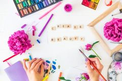 Top view Female Hands holding brush with Create beauty lettering, colorful painting materials and peony flowers on white. Background. Add colors to your life royalty free stock photo