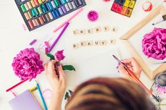 Top view Female Hands holding brush with Create beauty lettering, colorful painting materials and peony flowers on white. Background. Add colors to your life stock photo