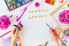 Top view Female Hands holding brush over blank canvas with Create beauty lettering, painting materials and flowers on white. Background. Add colors to your life stock images