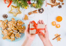 Top view female hands holding gift with red satin ribbon under white wooden table with gingerbred cookies, christmas tree branches. With decor, spices and Stock Images